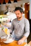 Молодой человек делая печенья дома Стоковая Фотография