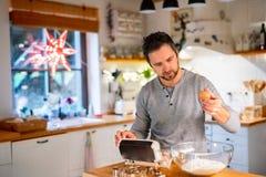 Молодой человек делая печенья дома Стоковые Фото