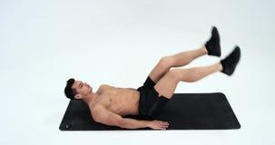 Молодой человек делая подбрюшные тренировки движение ноги сидя на половике Красная эпопея сток-видео