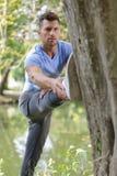 Молодой человек делая протягивать против дерева в парке Стоковое фото RF