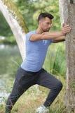 Молодой человек делая протягивать против дерева в парке Стоковая Фотография RF