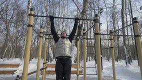 Молодой человек делая тягу вверх по тренировке на поперечине во время разминки спортзала зимы видеоматериал