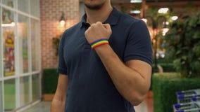 Молодой человек демонстрирует атрибут LGBT на руке стоковое фото