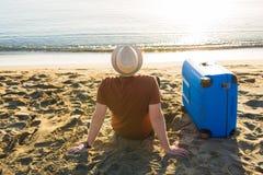 Молодой человек держа багаж на море Перемещение, летнее время, праздники и концепция людей стоковая фотография