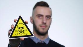Молодой человек держа ` ` знаков опасно на белой предпосылке видеоматериал