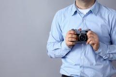 Молодой человек держа камеру стоя на серой предпосылке Стоковая Фотография RF