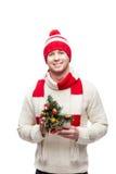 Молодой человек держа малую рождественскую елку Стоковое фото RF
