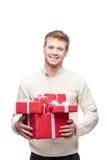 Молодой человек держа много красных подарков рождества стоковое фото rf