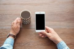 Молодой человек держа мобильный телефон с пустым экраном стоковое фото