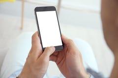 Молодой человек держа мобильный телефон с пустым экраном стоковая фотография rf