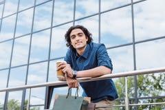 Молодой человек держа хозяйственные сумки и выпивая кофе от бумажного стаканчика Стоковые Фото