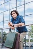 Молодой человек держа хозяйственные сумки и выпивая кофе от бумажного стаканчика Стоковое фото RF