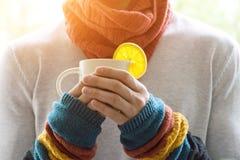 Молодой человек держа чашку чаю и лимон Холодный, холодный, заболевание Стоковые Изображения