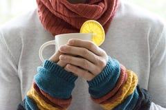 Молодой человек держа чашку чаю и лимон Холодный, холодный, заболевание Стоковые Фото
