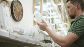Молодой человек держит 2 настенные часы и выбирает между ими в супермаркете сток-видео