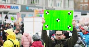 Молодой человек держит плакат с зеленым экраном на предпосылке толпы в демонстрации города сток-видео