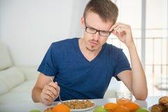 Молодой человек думал овсяную кашу во время завтрака стоковая фотография rf