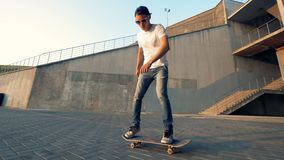 Молодой человек едет скейтборд и выполняет фокус с поворачивать вокруг на его акции видеоматериалы