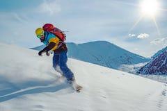Молодой человек едет сноуборд Нетронутый снег в горах стоковые изображения rf
