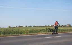 Молодой человек ехать электрический самокат стоковая фотография rf