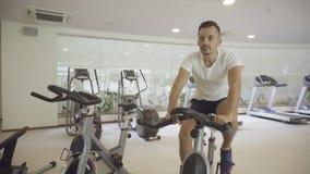 Молодой человек задействуя на велотренажере в спортзале сток-видео