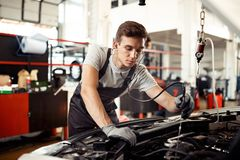 Молодой человек занятый с проверкой двигателя автомобиля: ремонт и обслуживание автомобиля стоковое фото rf