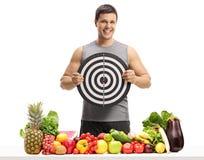 Молодой человек за таблицей при фрукт и овощ держа смолку Стоковое Изображение RF