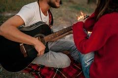 Молодой человек играет на гитаре и поет песню около девушки против backg стоковое фото rf