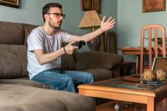 Молодой человек играя видеоигру держа беспроводной регулятор стоковое изображение rf