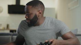 Молодой человек играя видеоигру дома Нервный парень держа станцию игры сток-видео