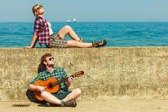 Молодой человек играя гитару к его подруге взморьем Стоковая Фотография