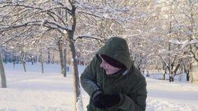 Молодой человек играя снежные комья в парке 4K видеоматериал