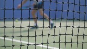 Молодой человек играя теннис с ракеткой тенниса на солнечный день движение медленное запачканный на переднем плане решетки 1920x1 сток-видео