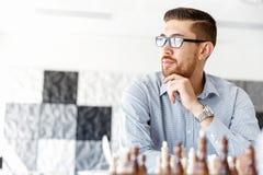 Молодой человек играя шахмат Стоковые Фотографии RF