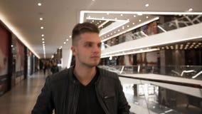 Молодой человек идя в торговый центр видеоматериал