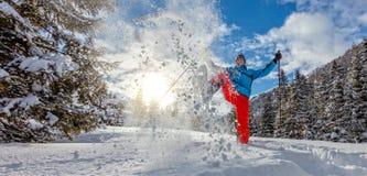 Молодой человек идя на snowshoes в снеге порошка стоковое фото rf