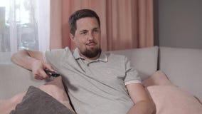 Молодой человек изменять каналы ТВ, используя дистанционное управление, сидя на софе видеоматериал