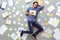 Молодой человек изолированный на серой предпосылке при бумаги и примечания спать с книгой стоковое изображение