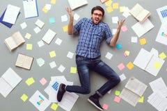 Молодой человек изолированный на серой предпосылке с бумагами и примечаниями неудовлетворёнными стоковая фотография rf