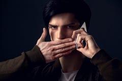 Молодой человек изолированный на сером телефонном звонке концепции студии стены стоковое изображение
