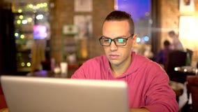 Молодой человек испанской этничности используя портативный компьютер на уютной кофейне Концепция технологий glasses men акции видеоматериалы