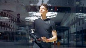 Молодой человек использует его smartphone с искусственной рукой Человек будущей концепции