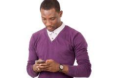 Молодой человек использует умный телефон изолированный на белой предпосылке стоковое фото