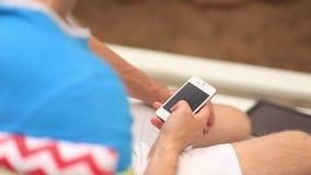 Молодой человек используя его телефон видеоматериал