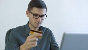 Молодой человек используя кредитную карточку онлайн видеоматериал