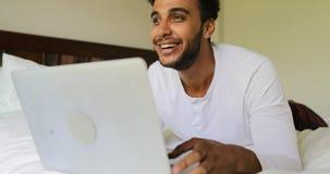 Молодой человек используя портативный компьютер лежа на беседовать Гая испанца кровати счастливый усмехаясь онлайн в утре спальни видеоматериал