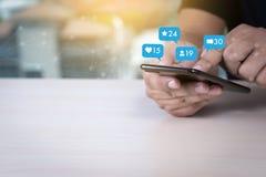 Молодой человек используя средства массовой информации умного телефона социальные и социальную сеть Марк стоковые изображения