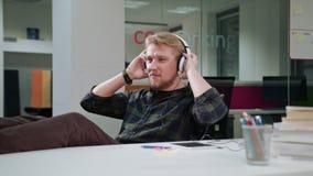 Молодой человек используя таблетку и слушающ к музыке стоковые фото