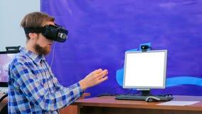 Молодой человек используя шлемофон виртуальной реальности перед белым пустым монитором стоковые изображения rf