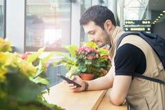 Молодой человек используя smartphone в салоне отклонения Стоковые Фото